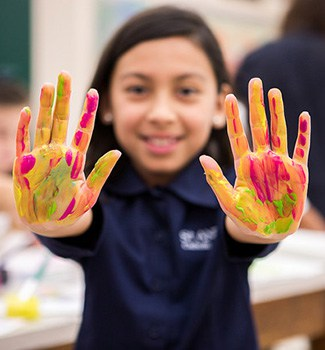 Student with paint on her hands